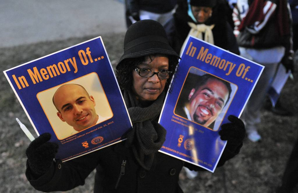 An AFGE member holds up a sign with the images of Eric Williams and Osvaldo Albarati - two Bureau of Prison employees who were murdered on the job.